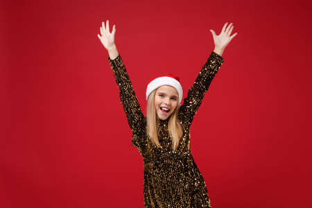 Cheerful little blonde kid girl 12-13 years old in glitter party outfit Santa hat isolated on red wall background. Happy New Year 2020 celebration holiday concept. Mock up copy space. Rising hands.