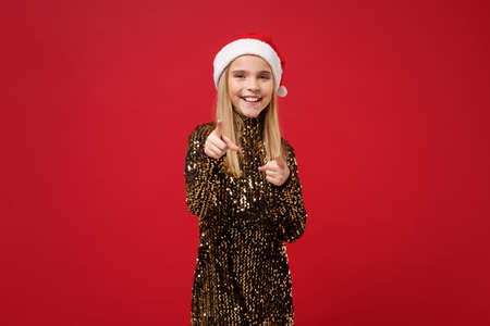 Smiling little kid girl 12-13 years old in glitter party outfit Santa hat isolated on red background. Happy New Year 2020 celebration holiday concept. Mock up copy space. Pont index fingers on camera.