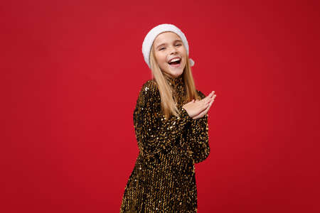 Laughing little blonde kid girl 12-13 years old in glitter party outfit Santa hat isolated on red background. Happy New Year 2020 celebration holiday concept. Mock up copy space. Holding hands folded.
