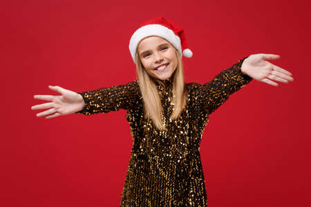 Pleasant little girl 12-13 years old in glitter party outfit Santa hat isolated on red background. Happy New Year 2020 celebration holiday concept. Mock up copy space. Stand with outstretched hands.