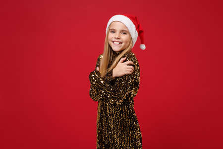Smiling little blonde kid girl 12-13 years old in glitter party outfit Santa hat isolated on red wall background. New Year 2020 celebration holiday concept. Mock up copy space. Holding hands crossed.