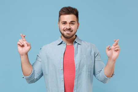 Young bearded guy 20s in casual shirt isolated on pastel blue background. People lifestyle concept. Mock up copy space. Waiting for special moment, keeping fingers crossed, making wish, biting lips. Stock fotó