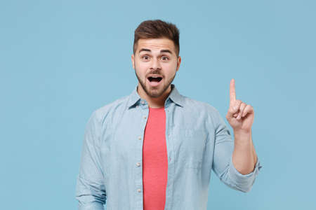 Excited young bearded guy 20s in casual shirt posing isolated on pastel blue wall background studio portrait. People lifestyle concept. Mock up copy space. Holding index finger up with great new idea.
