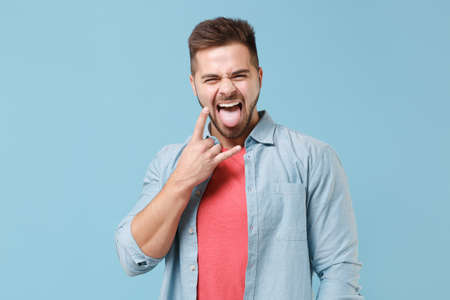 Crazy young bearded guy 20s in casual shirt posing isolated on pastel blue background. People lifestyle concept. Mock up copy space. Depicting heavy metal rock sign, horns up gesture, showing tongue.