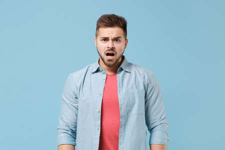 Shocked perplexed young bearded guy in casual shirt posing isolated on pastel blue background studio portrait. People sincere emotions lifestyle concept. Mock up copy space. Looking camera, swearing.