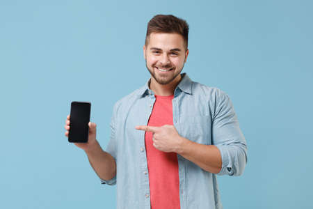 Smiling young bearded guy 20s in casual shirt posing isolated on pastel blue background. People lifestyle concept. Mock up copy space. Pointing index finger on mobile phone with blank empty screen.