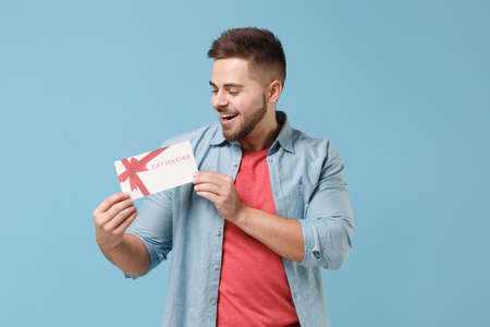 Cheerful young bearded guy 20s in casual shirt posing isolated on pastel blue wall background studio portrait. People sincere emotions lifestyle concept. Mock up copy space. Hold gift certificate. Stock Photo