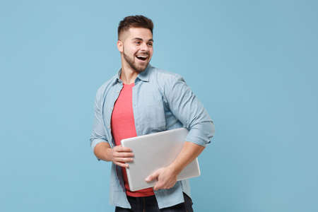 Excited young bearded guy 20s in casual shirt posing isolated on pastel blue background studio portrait. People emotions lifestyle concept. Mock up copy space. Hold laptop pc computer, looking aside.