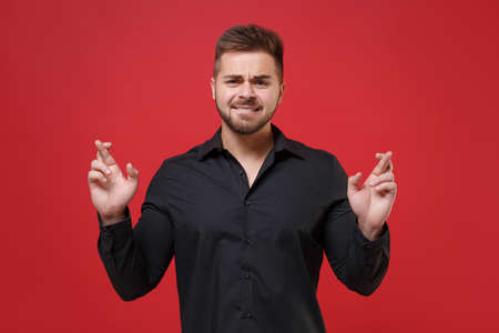 Pleading young bearded guy in classic black shirt isolated on red background. People lifestyle concept. Mock up copy space. Waiting for special moment keeping fingers crossed making wish, biting lips.