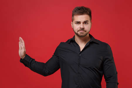 Dissatisfied young bearded guy 20s in classic black shirt posing isolated on red wall background studio portrait. People lifestyle concept. Mock up copy space. Showing stop gesture with palm aside.