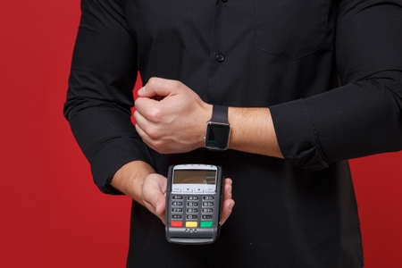 Cropped image of young guy in black shirt isolated on red background. People lifestyle concept. Wearing smart watch on hand, hold bank payment terminal to process and acquire credit card payments.