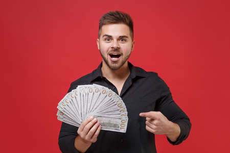 Amazed young bearded guy in classic black shirt posing isolated on red background studio. People lifestyle concept. Mock up copy space. Pointing index finger on fan of cash money in dollar banknotes.