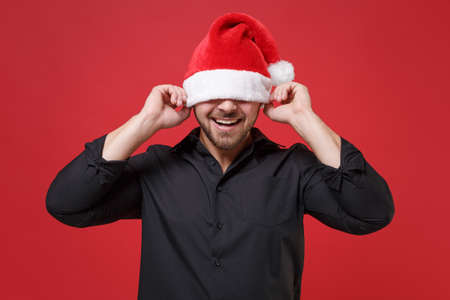 Funny young bearded Santa man in classic black shirt posing isolated on red wall background in studio. Happy New Year celebration holiday concept. Mock up copy space. Covering eyes with Christmas hat.