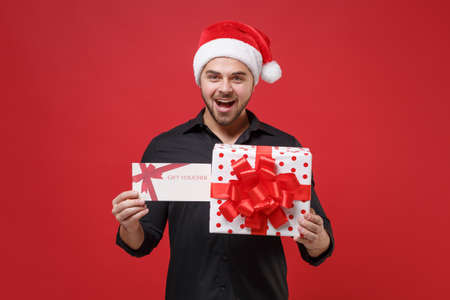 Shocked Santa man in classic black shirt, Christmas hat isolated on red background. Happy New Year celebration holiday concept. Mock up copy space. Hold present box with ribbon bow, gift certificate.