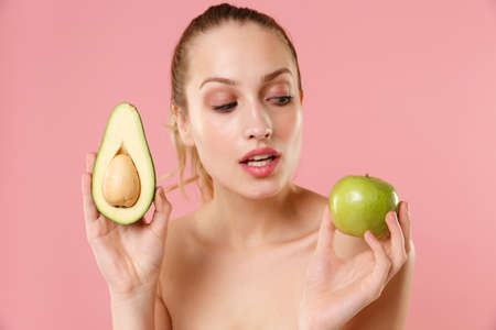 Close up half naked woman 20s perfect skin nude make up blue eyes hold in hand ripe avocado apple isolated on pastel pink background studio portrait. Skin care healthcare cosmetic procedures concept. Imagens
