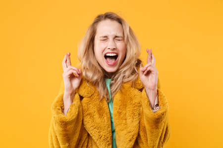 Crazy young woman in yellow fur coat isolated on orange background. People lifestyle concept. Mock up copy space. Waiting for special moment, keeping fingers crossed eyes closed making wish screaming.