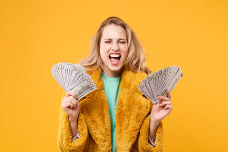 Crazy young blonde woman girl in yellow fur coat isolated on orange background. People lifestyle concept. Mock up copy space. Hold fan of cash money in dollar banknotes, screaming keeping eyes closed.
