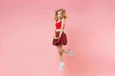 Smiling young blonde woman girl in red clothes posing isolated on pastel pink background studio portrait. People sincere emotions lifestyle concept. Mock up copy space. Jumping, looking camera.