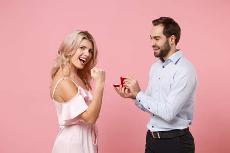 Couple two guy girl in party outfit celebrating posing isolated on pastel pink background. Valentines Day Womens Day birthday holiday concept. Hold gift box with proposal ring doing winner gesture.