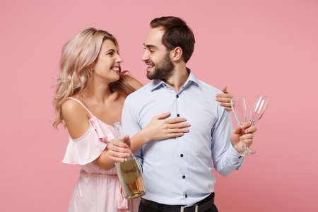 Smiling young couple two guy girl in party outfit celebrating posing isolated on pastel pink background. Valentines Day Womens Day birthday holiday party concept. Holding glass bottle of champagne.
