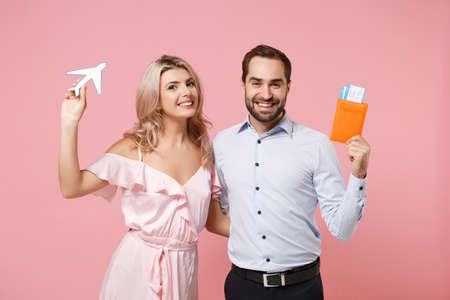 Smiling young couple two guy girl in party outfit celebrating posing isolated on pink background. Valentines Day, Womens Day birthday holiday concept. Hold passport boarding pass, ticket, air plane. Archivio Fotografico
