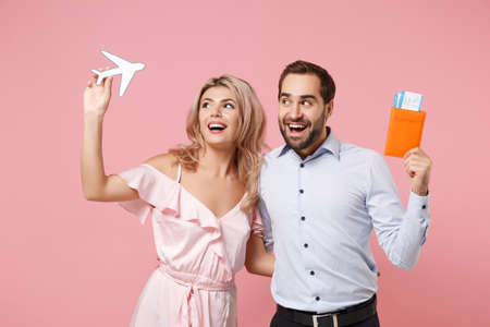 Cheerful young couple two guy girl in party outfit celebrating posing isolated on pink background. Valentines Day, Womens Day birthday holiday concept. Hold passport boarding pass ticket, air plane. Archivio Fotografico