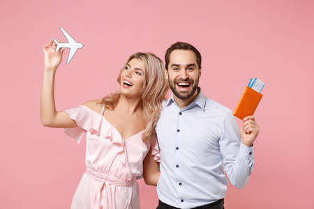 Funny young couple two guy girl in party outfit celebrating posing isolated on pink background. Valentines Day, Womens Day birthday holiday concept. Hold passport, boarding pass, ticket, air plane. Archivio Fotografico