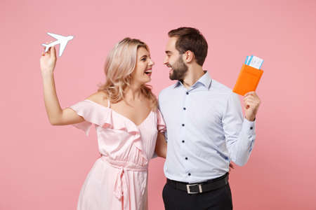 Happy young couple two guy girl in party outfit celebrating posing isolated on pink background. Valentines Day, Womens Day birthday holiday concept. Hold passport boarding pass ticket, air plane. Archivio Fotografico