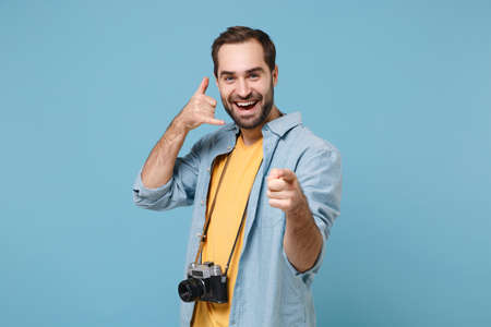 Traveler tourist man in yellow summer clothes with photo camera isolated on blue background. Male passenger traveling abroad on weekends. Air flight journey Doing phone gesture like says call me back. Stock fotó