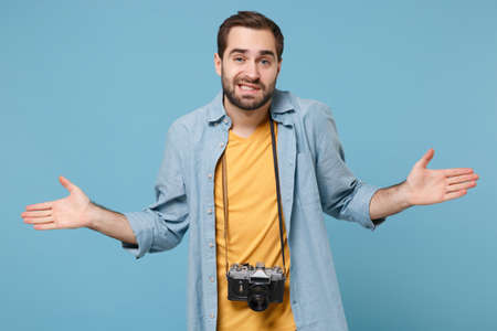 Perplexed traveler tourist man in yellow summer casual clothes with photo camera isolated on blue background. Male passenger traveling abroad on weekends. Air flight journey concept. Spreading hands.
