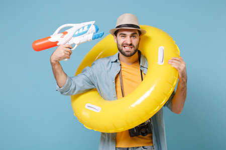 Traveler tourist man in yellow clothes with photo camera isolated on blue background. Travel on weekends. Air flight journey. Hold inflatable ring point water gun to head as if he about shoot himself.