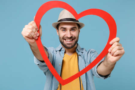 Smiling traveler tourist man in summer yellow clothes with photo camera isolated on blue background. Passenger traveling abroad on weekends. Air flight journey concept. Holding red big wooden heart.