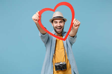 Laughing traveler tourist man in casual yellow clothes with photo camera isolated on blue background. Passenger traveling abroad on weekends. Air flight journey concept. Holding red big wooden heart.