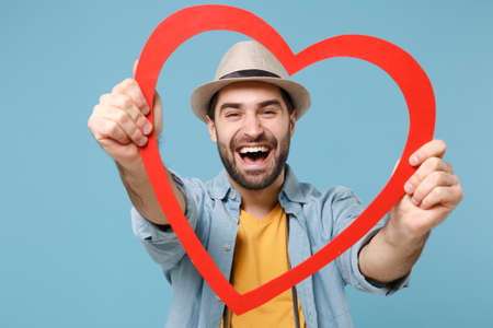 Cheerful traveler tourist man in casual yellow clothes with photo camera isolated on blue background. Passenger traveling abroad on weekends. Air flight journey concept. Holding red big wooden heart.