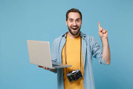 Excited traveler tourist man in casual clothes with photo camera isolated on blue background. Passenger traveling on weekend. Air flight journey. Working on laptop booking hotel point index finger up.