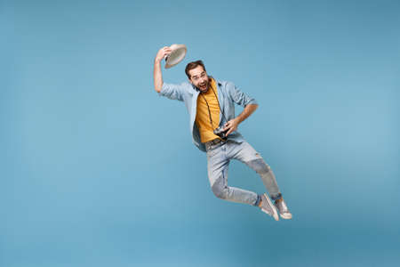 Funny traveler tourist man in yellow summer casual clothes with photo camera isolated on blue background. Male passenger traveling abroad on weekend. Air flight journey concept. Jumping, rising hat.