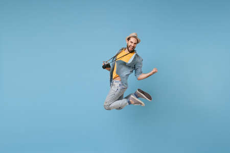 Joyful traveler tourist man in yellow casual clothes with photo camera isolated on blue background. Male passenger traveling abroad on weekend. Air flight journey concept Jumping doing winner gesture.