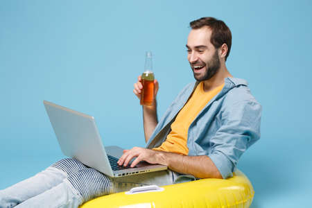 Funny traveler tourist man in yellow clothes isolated on blue background. Passenger traveling abroad on weekend. Air flight journey concept. Sitting in inflatable ring work on laptop hold beer bottle.