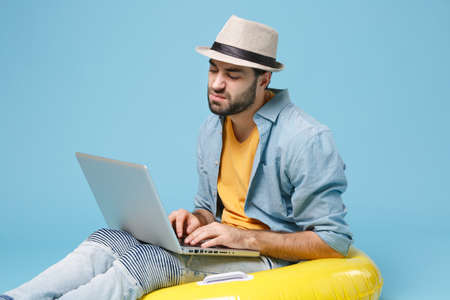Displeased traveler tourist man in yellow clothes isolated on blue background. Passenger traveling abroad on weekend. Air flight journey concept. Sit in inflatable ring work on laptop booking hotel.