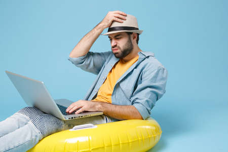 Puzzled traveler tourist man in yellow clothes isolated on blue background. Passenger traveling abroad on weekends. Air flight journey concept. Sit in inflatable ring, work on laptop, booking hotel.