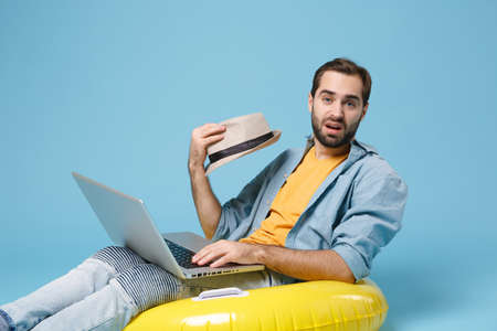 Perplexed traveler tourist man in yellow clothes isolated on blue background. Passenger traveling abroad on weekends. Air flight journey concept. Sit in inflatable ring work on laptop booking hotel.