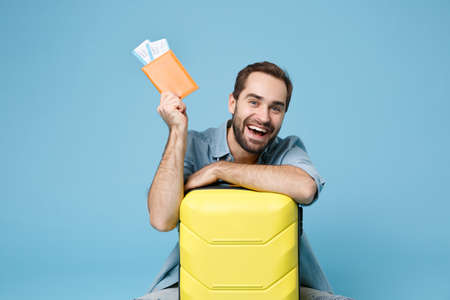 Funny traveler tourist man in yellow clothes isolated on blue background. Passenger traveling abroad on weekend. Air flight journey concept. Sitting near suitcase hold passport boarding pass tickets.