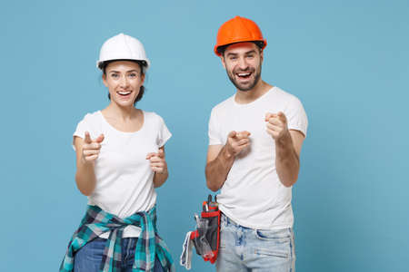 Couple woman man in casual clothes protective helmet hardhat isolated on blue background. Instruments accessories for renovation apartment room. Repair home concept. Pointing index fingers on camera.