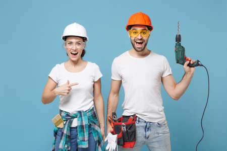 Excited couple woman man in protective helmet hardhat pointing index finger on electric drill isolated on blue background. Instruments accessories for renovation apartment room. Repair home concept.