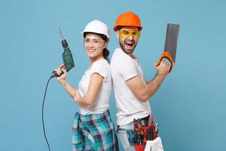 Excited couple woman man in protective helmet hardhat hold electric drill saw isolated on blue background. Instruments accessories renovation apartment room. Repair home concept. Stand back to back. Reklamní fotografie
