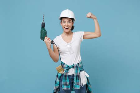 Laughing young woman in protective helmet hardhat hold electric drill isolated on blue background. Instruments accessories for renovation apartment room. Repair home concept. Showing biceps, muscles.