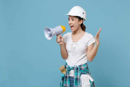 Excited young woman in protective helmet hardhat scream in megaphone isolated on blue background in studio. Instruments accessories for renovation apartment room. Repair home concept. Spreading hands.
