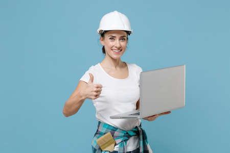 Smiling woman in protective helmet hardhat working on laptop pc computer isolated on blue wall background. Instruments accessories for renovation apartment room. Repair home concept. Showing thumb up.