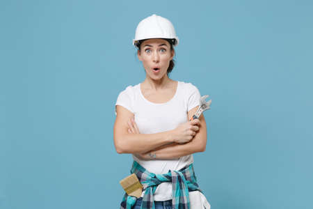 Amazed young woman in protective helmet hardhat hold adjustable wrench isolated on blue background. Instruments accessories for renovation apartment room. Repair home concept. Holding hands crossed.