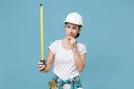 Puzzled young woman in protective helmet hardhat hold measure tape isolated on blue background. Instruments accessories for renovation apartment room. Repair home concept. Put hand prop up on chin.